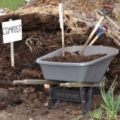 Pile of compost with sign and wheelbarrow