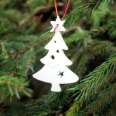 A Christmas tree ornament shaped like a Christmas tree on a spruce Christmass tree.